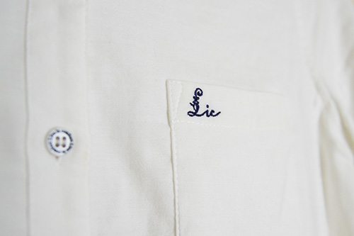 フェリシモリブインコンフォート重ね着してももたつかない! ストレッチガーゼ×カットソーの伸びシャツ、オフホワイトの胸ポケット付近アップ。リブインコンフォートのロゴ刺しゅうがはいっています。